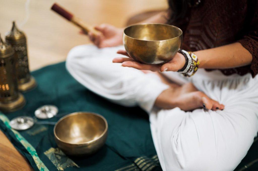 Frau im Lotussitz mit Klangschale in der Hand